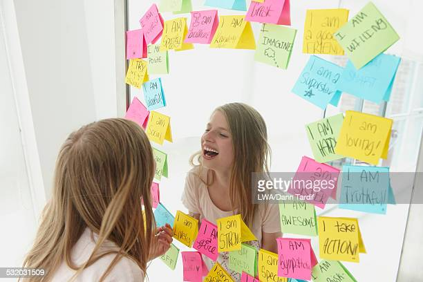 Caucasian girl laughing in mirror with adhesive notes