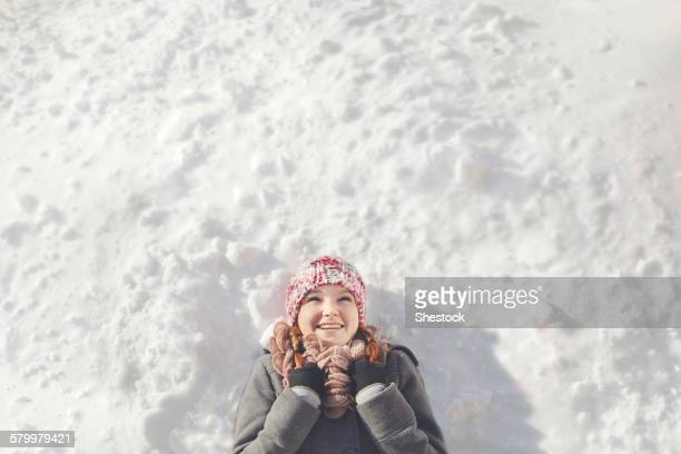 Caucasian girl laying in snow