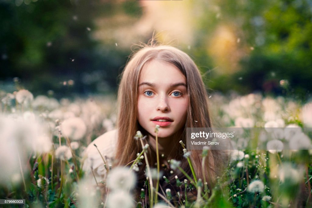 Caucasian girl laying in tall grass and dandelions