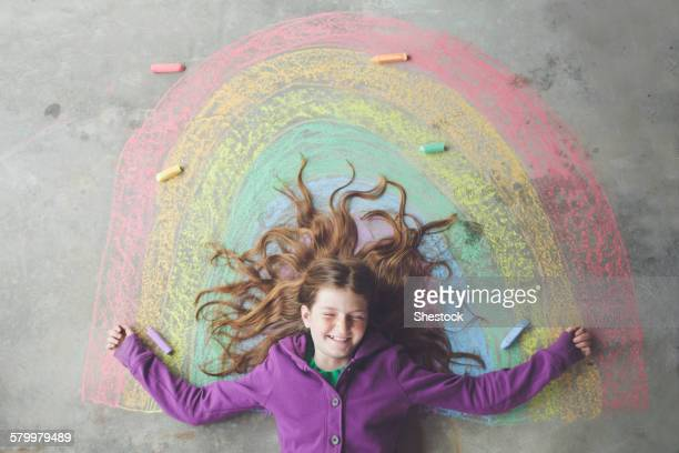 Caucasian girl laying on chalk rainbow