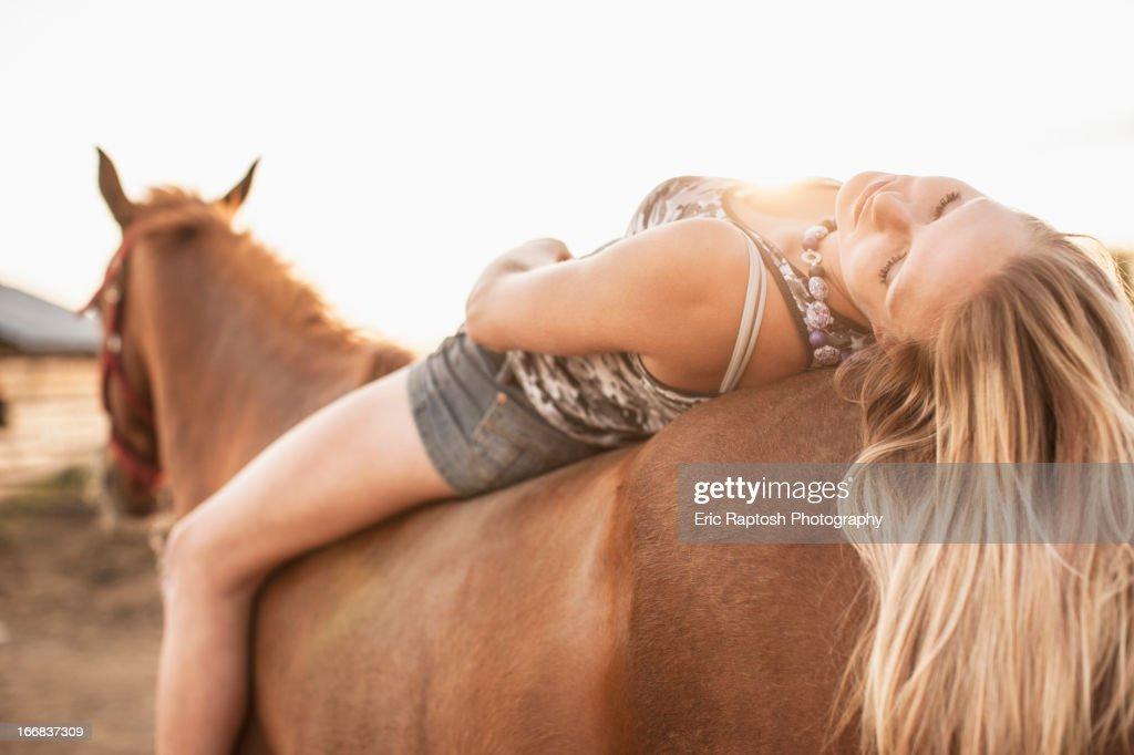 Caucasian girl laying on horse : Stock Photo