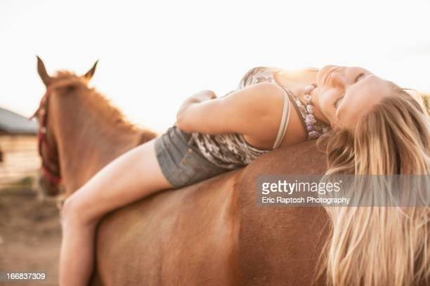 Caucasian girl laying on horse
