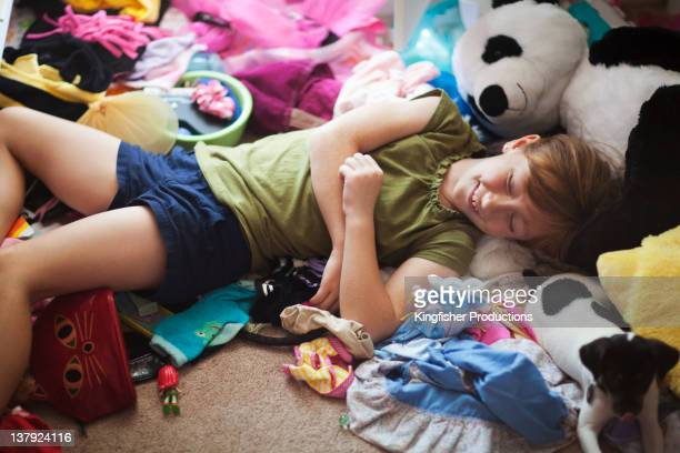 Caucasian girl laying on messy floor