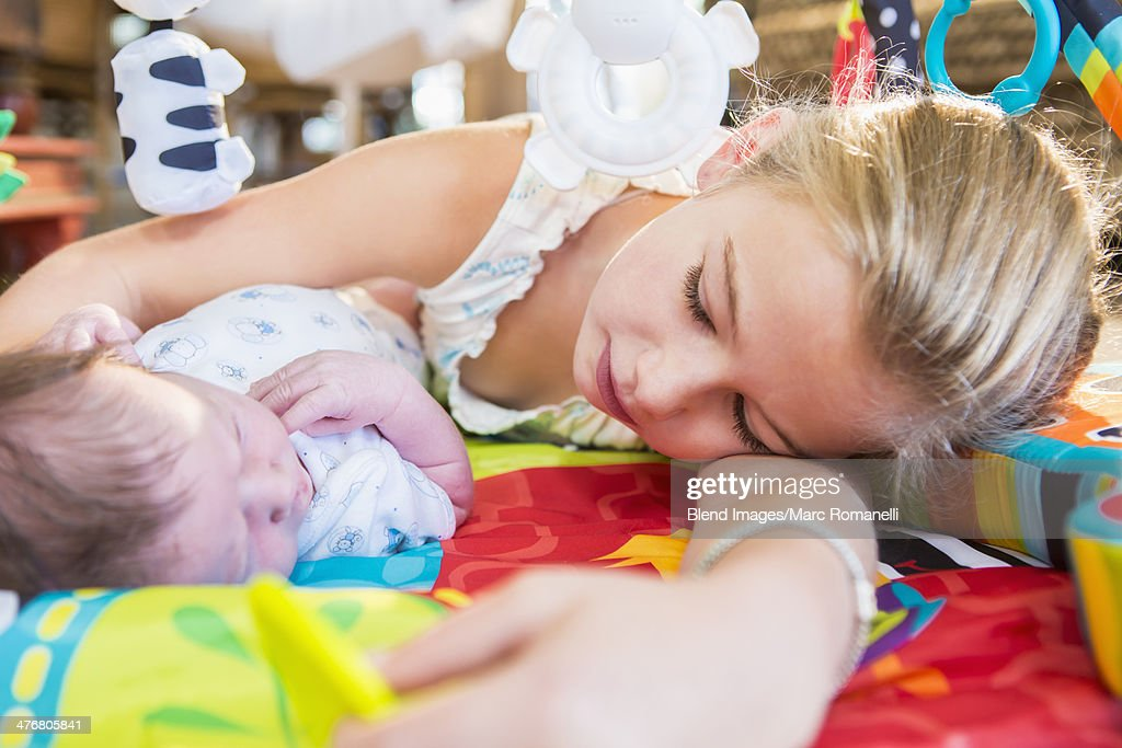 Caucasian girl laying with newborn baby brother : Foto de stock