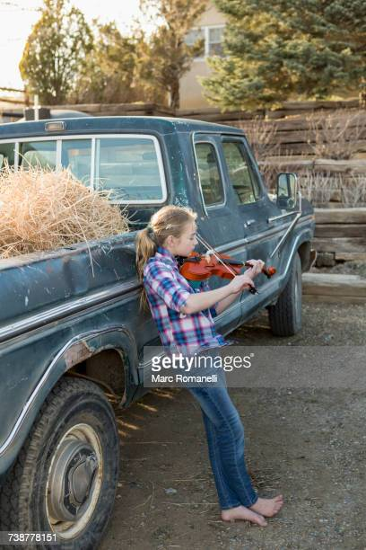 Caucasian girl leaning on truck playing violin