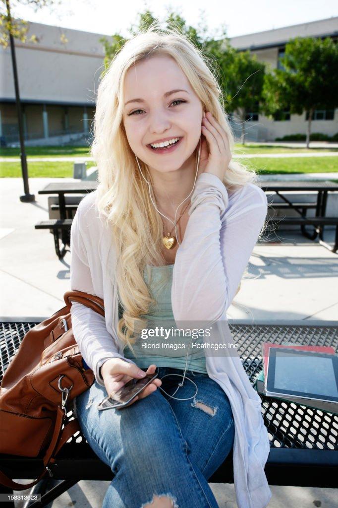 Caucasian girl listening to mp3 player : Stock Photo