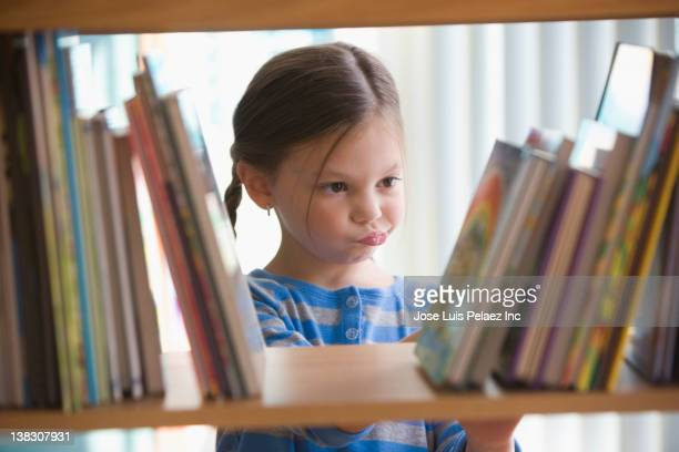 Caucasian girl looking at books on shelf