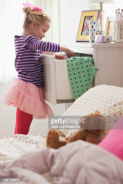 Caucasian girl looking in dresser drawer
