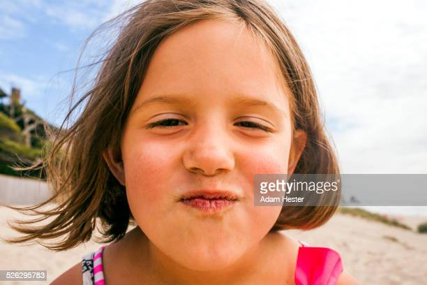 Caucasian girl making face on beach