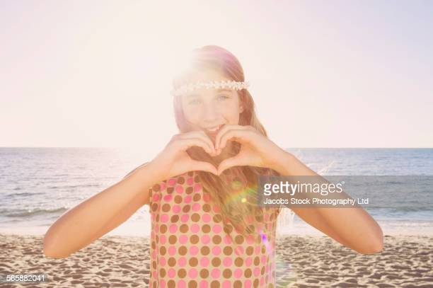 Caucasian girl making heart shape with hands on beach
