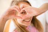 Caucasian girl making heart shape with hands
