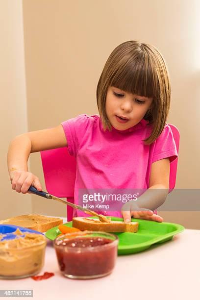 Caucasian girl making sandwich in kitchen
