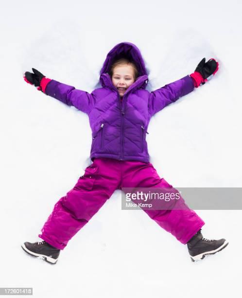 Caucasian girl making snow angel outdoors