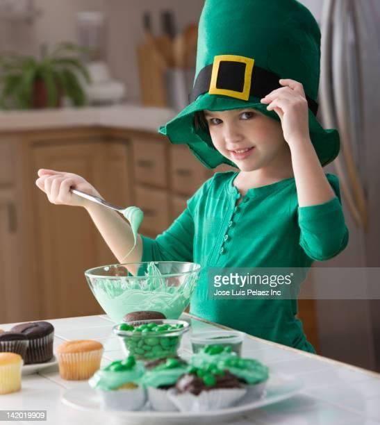 Caucasian girl making St. Patrick's cupcakes
