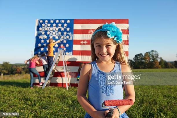 Caucasian girl painting American flag in field