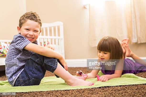 Caucasian girl painting brother's toes