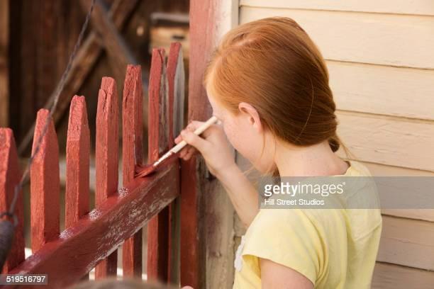 Caucasian girl painting house