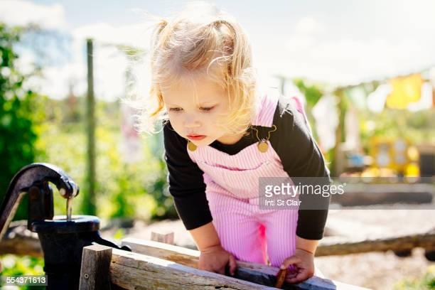 Caucasian girl peering over wooden fence