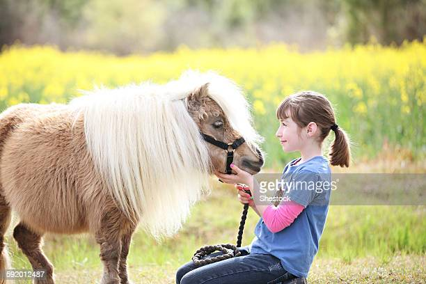 Caucasian girl petting pony in rural field