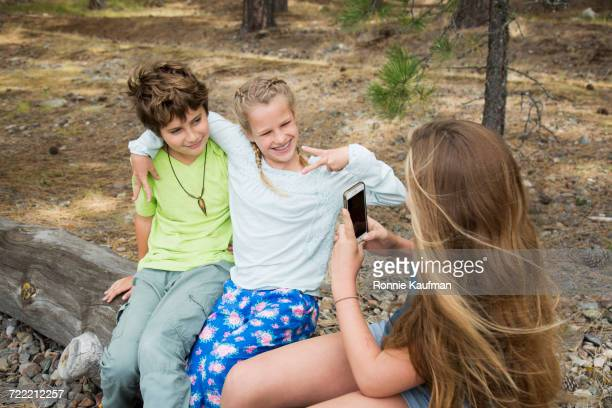 Caucasian girl photographing friends with cell phone