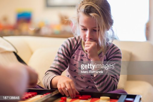 Caucasian girl playing backgammon on sofa : Stock Photo
