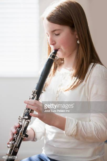 Caucasian girl playing clarinet
