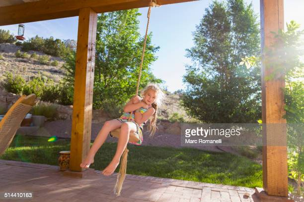 Caucasian girl playing on rope swing