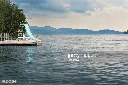 Caucasian girl playing on slide over remote lake