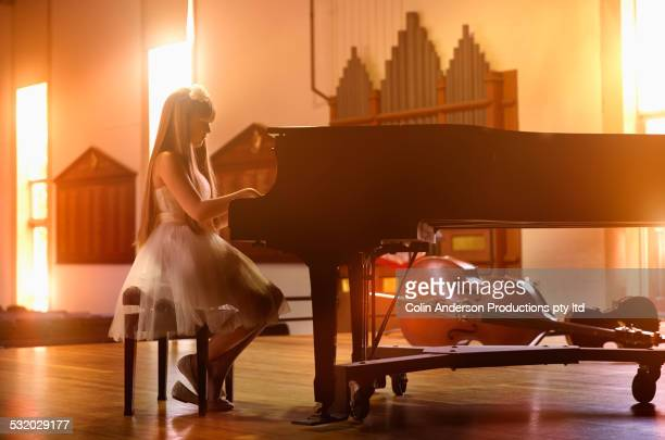 Caucasian girl playing piano on stage