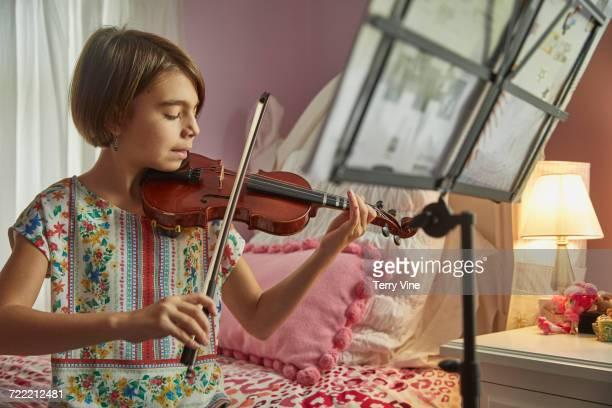 Caucasian girl playing violin in bedroom