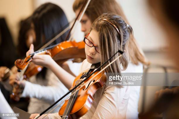Caucasian girl playing violin in music class