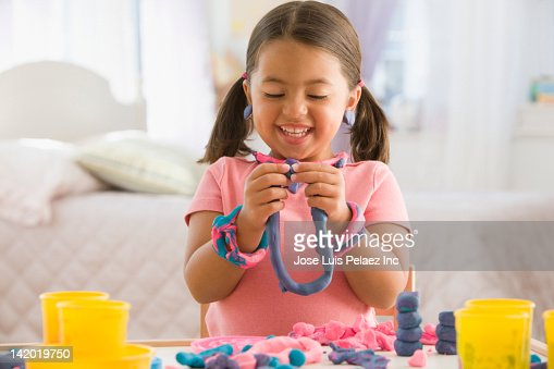 Caucasian girl playing with clay