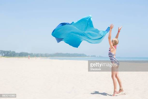 Caucasian girl playing with fabric on beach