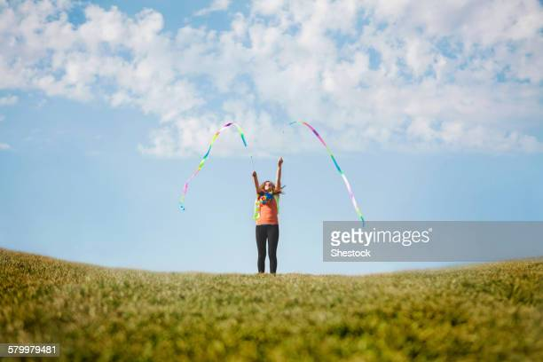 Caucasian girl playing with ribbons on hilltop