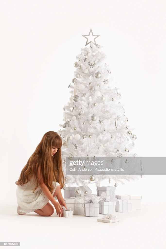 Caucasian girl putting gifts under Christmas tree : Stock Photo