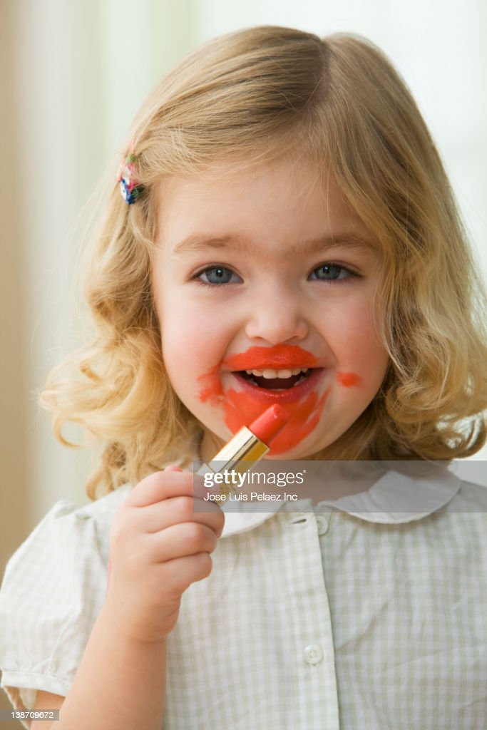 Caucasian Girl Putting On Lipstick Stock Photo