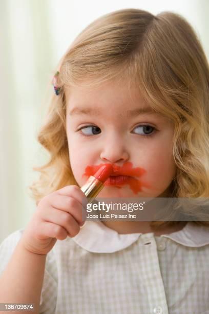 Caucasian girl putting on lipstick