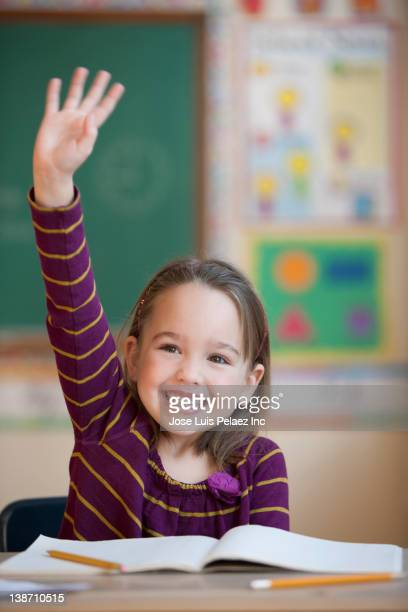 Caucasian girl raising hand in classroom