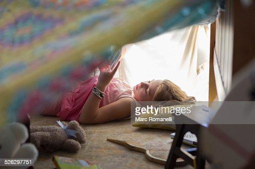 Caucasian girl reading in blanket fort