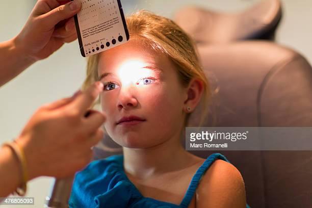 Caucasian girl receiving eye exam