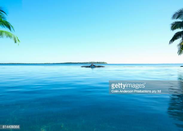 Caucasian girl relaxing in still pool overlooking ocean