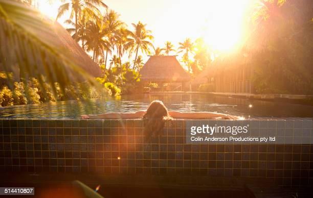 Caucasian girl relaxing in swimming pool