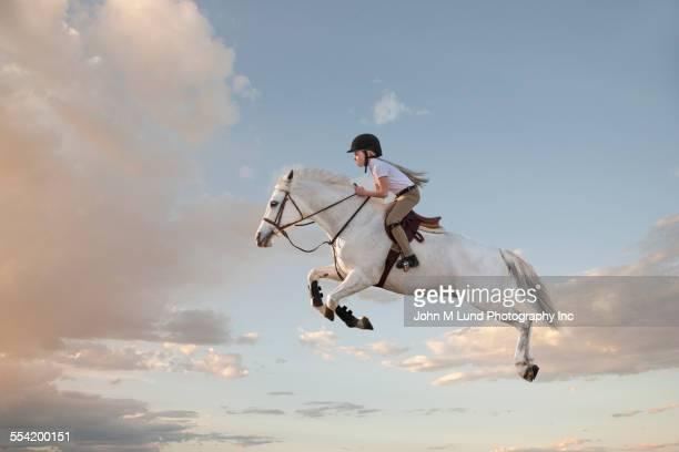 Caucasian girl riding horse in cloudy sky