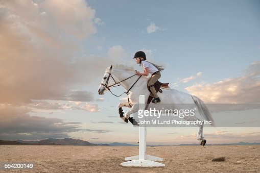 Caucasian girl riding horse over gable in race