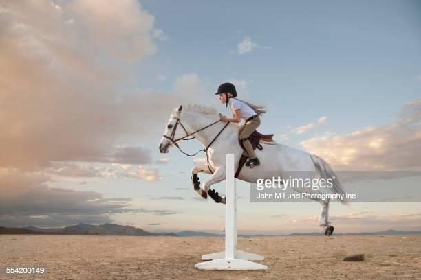 Caucasian girl riding horse over gable in race