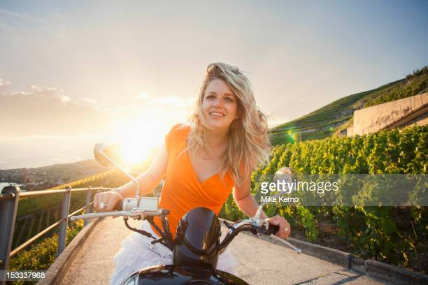 Caucasian girl riding scooter in vineyard
