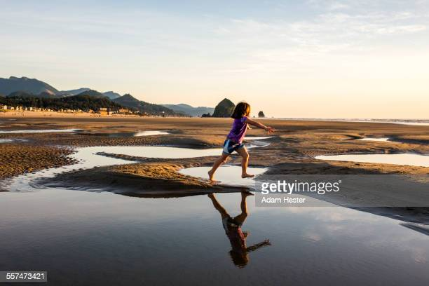 Caucasian girl running in tide pools on beach, Cannon Beach, Oregon, United States