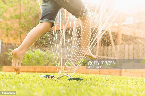 Caucasian girl running through sprinkler in backyard