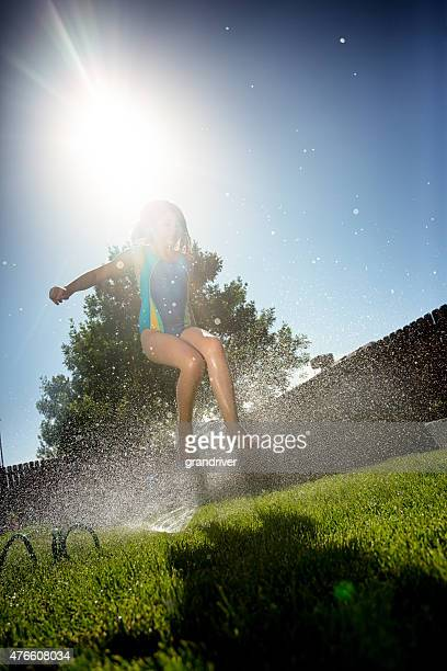 Caucasian Girl Running Through Sprinklers