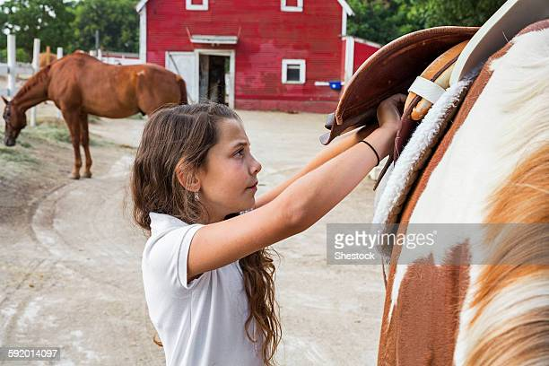 Caucasian girl saddling horse on ranch